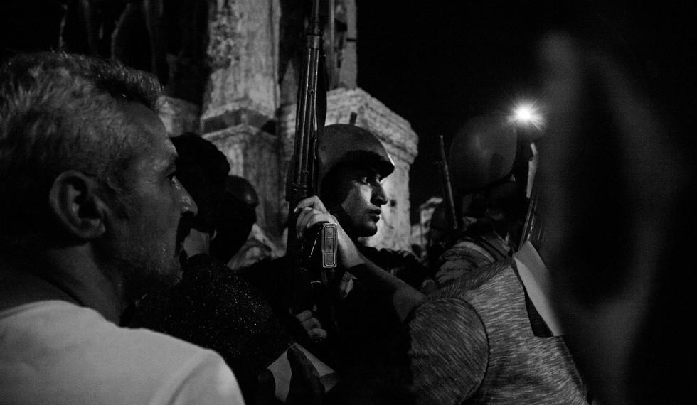 Un contingente de soldados ha acudido a la plaza Taksim para apoyar el golpe de Estado. De pronto, se encuentran rodeados por miembros del gentío que están en contra del golpe y por partidarios del presidente Erdoğan. La tensión y el miedo de este soldado se van haciendo palpables entre los militares a medida que asumen su inferioridad e intentan mantenerse impasibles entre una multitud que los insulta. | Kalpesh Latigra